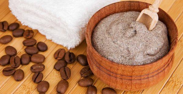 Кофейно-содовый скраб в деревянной миске, кофейные зерна и белое полотенце