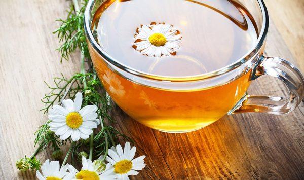 Отвар ромашки в чашке и цветы ромашки на деревянном столе