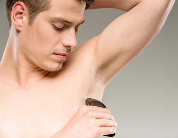 Мужчина наносит дезодорант