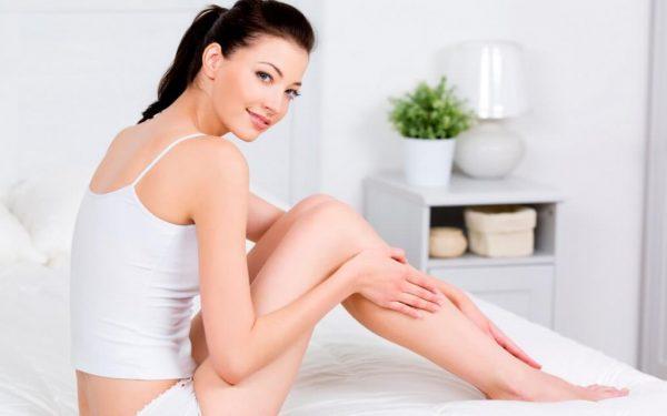 Девушка наносит крем на ноги