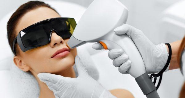 Девушка в защитных очках на процедуре лазерной эпиляции лица