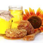 Мёд в банках, соты, цветок и деревянная ложка