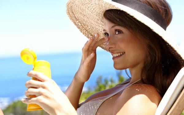 Женщина мажет лицо солнцезащитным кремом