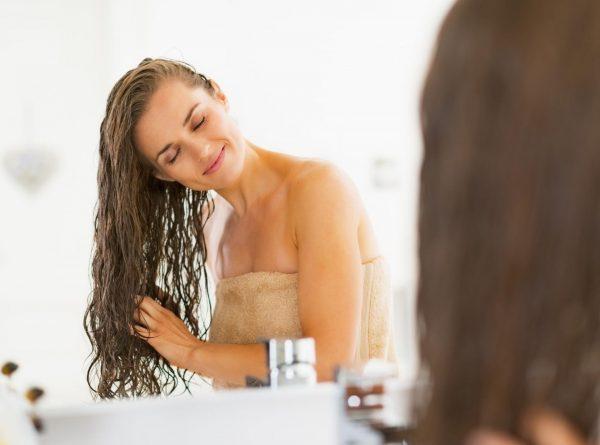 Девушка с влажными волосами напротив зеркала