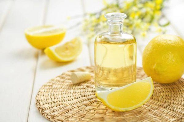 Лимонное масло в бутылке и лимоны