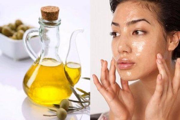 Бутылка оливкового масла и женщина наносящая его на лицо