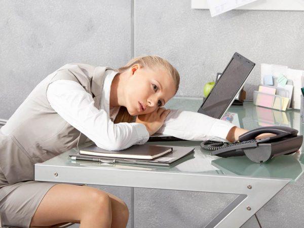 Уставшая девушка лежит на рабочем столе