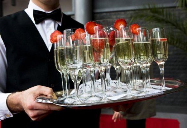 Официант несёт поднос с бокалами шампанского