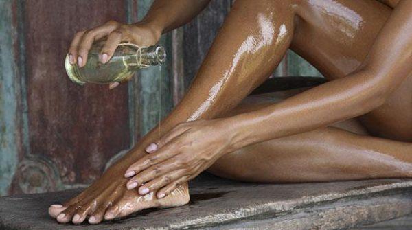 Девушка льёт масло на ногу