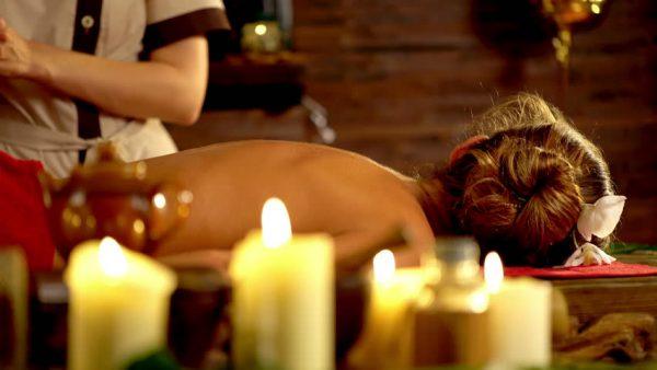Девушка на массажном столе и свечи