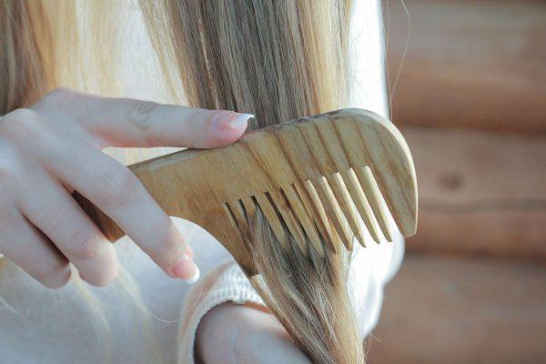 Девушка расчёсывает волос деревянным гребнем
