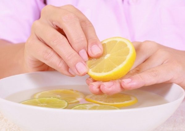 Руки девушки и ванночка для ногтей с лимоном