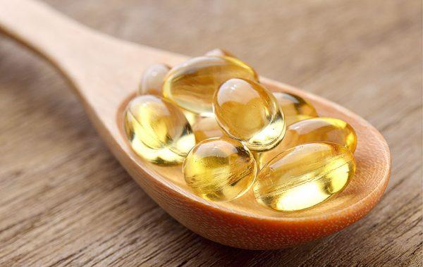 Витамин А в капсулах на деревянной ложке