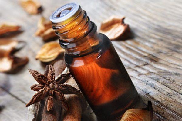 Анисовое масло в тёмном флаконе и растение