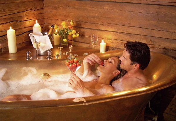 Женщина и мужчина в ванне с клубникой