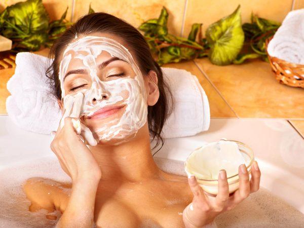 девушка принимает ванну с косметической маской на лице
