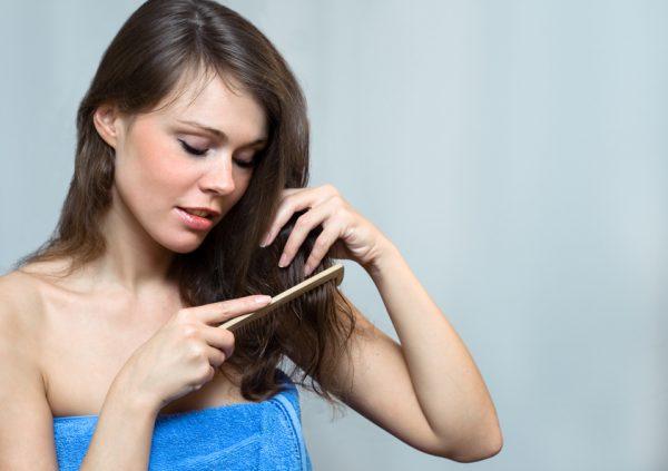 Девушка расчёсывает волосы