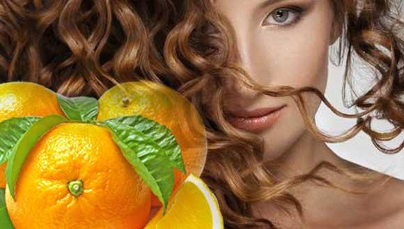 девушка с шикарными локонами и апельсины