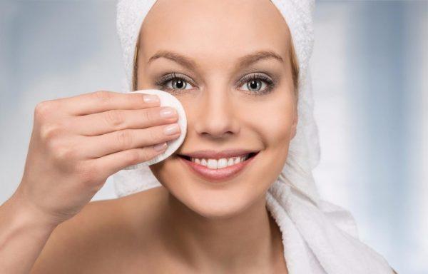 Девушка снимает макияж с помощью ватного диска и миндального масла