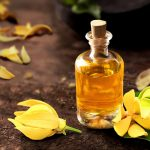 Эфирное масло иланг-иланга в прозрачном флаконе и цветы