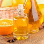 Эфирное масло апельсина в прозрачном флаконе и плоды