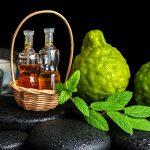Эфирное масло бергамота в прозрачных флаконах и растение