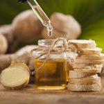 Эфирное масло имбиря в прозрачном флаконе и растение