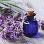 Эфирное масло лаванды в синем флаконе и цветы