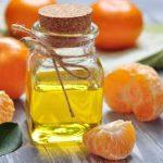 Эфирное масло мандарина в прозрачном флаконе и плоды
