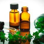 Эфирное масло майорана в тёмном флаконе и растение