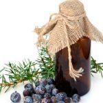 Эфирное масло можжевельника в тёмном флаконе и растение