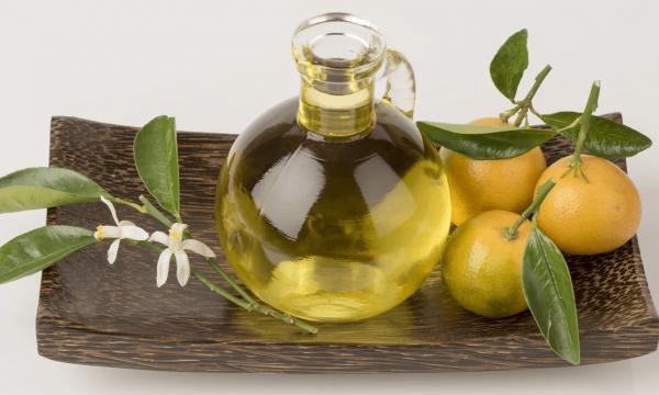 Эфирное масло петитгрейна в прозрачной ёмкости и плоды