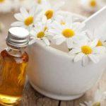 Эфирное масло ромашки в прозрачном флаконе и цветы