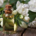 Эфирное масло жасмина в прозрачном флаконе и цветы