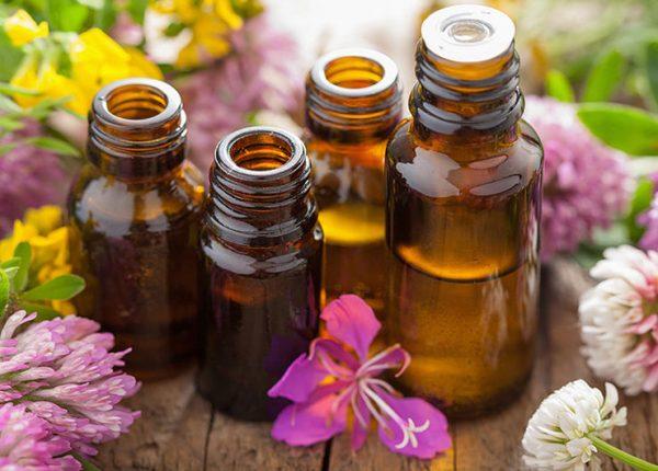 Эфирные масла в тёмных флаконах и цветы