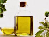 Касторовое масло в прозрачной бутылке и растение