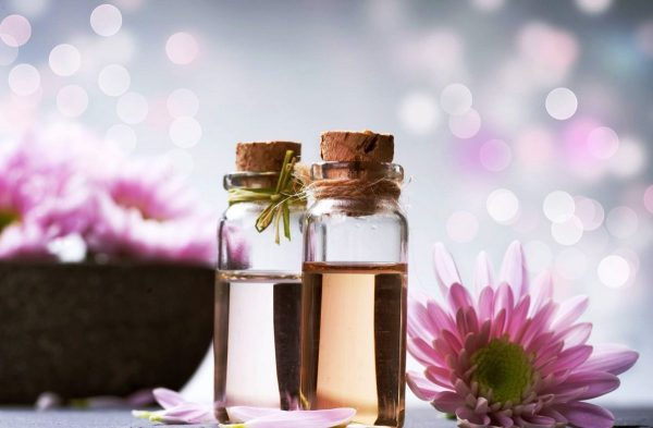 Эфирные масла в прозрачных флаконах и цветы