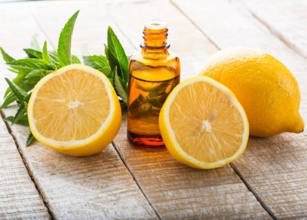Лимонное масло в тёмном флаконе и плоды в разрезе