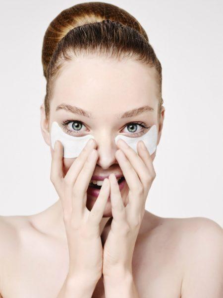 Девушка делает маску на коже вокруг глаз
