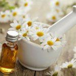 Масло ромашки в прозрачном флаконе и цветы