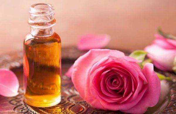 Масло розы в прозрачном флаконе и розовые цветы