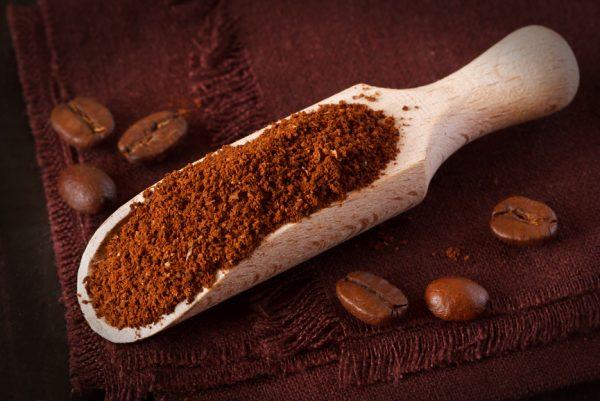Молотый кофе на деревянной лопаточке