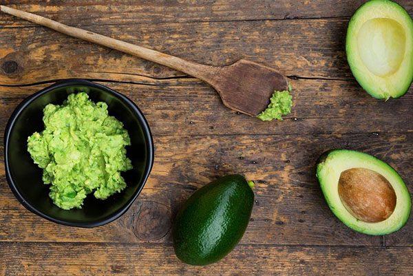 Мякоть авокадо в тёмной ёмкости и плоды в разрезе