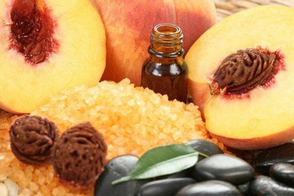 Персиковое масло в тёмном флаконе и плоды в разрезе