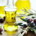 Оливковое масло в прозрачной бутылке и растение