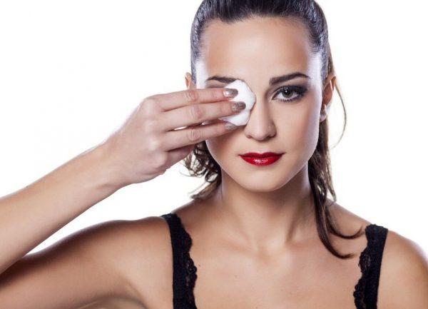 Девушка удаляет макияж с лица с помощью ваты