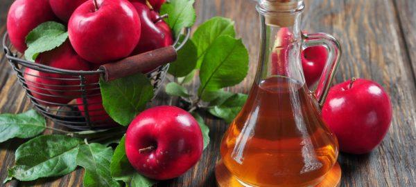 Яблочный уксус в прозрачной ёмкости и плоды
