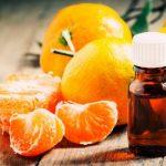 Эфирное масло мандарина в тёмном флаконе и фрукты