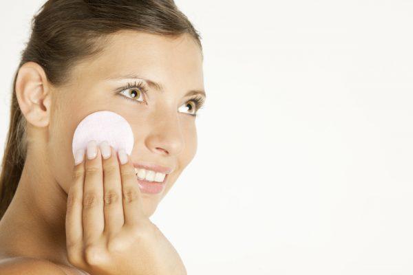 Девушка снимает макияж с лица ватным диском