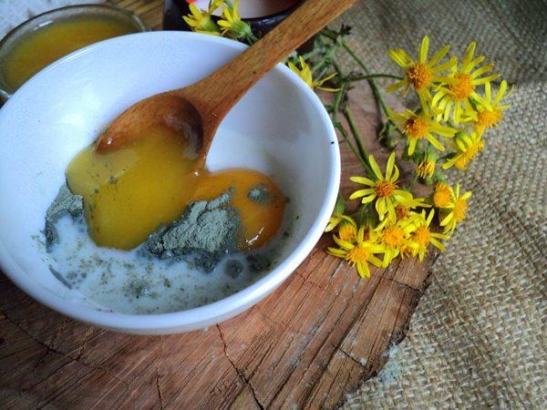 Голубая глина, желток и мёд в тарелке